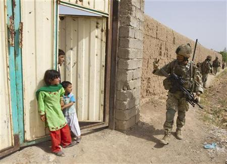 A British Army soldier waves to Afghan children during a patrol outside Patrol Base Chilli near Lashkar Gah in Helmand province